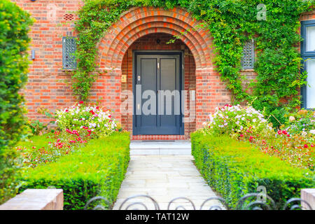 Front door of an English cottage decorated with garden plants and flowers in Hampstead, London - Stock Image