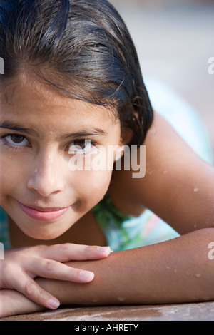 young latin girl in a bathing suit lying on the ground by the swimming pool - Stock Image