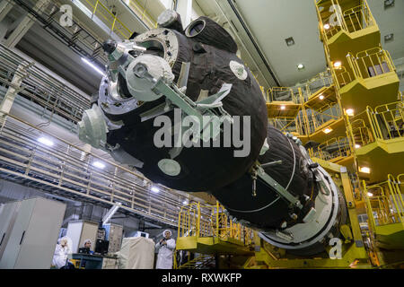 The Russian Soyuz MS-12 spacecraft is lowered into position for encapsulation into the nose fairing of the booster rocket in the Integration Building at the Baikonur Cosmodrome March 6, 2019 in Baikonur, Kazakhstan. The Expedition 59 crew: Nick Hague and Christina Koch of NASA and Alexey Ovchinin of Roscosmos will launch March 14th for a six-and-a-half month mission on the International Space Station. - Stock Image