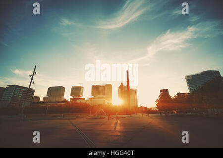 Wide angle shot of dramatic sunset with flare and godrays near  in Barcelona Forum district with distant residential - Stock Image