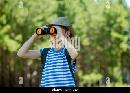 Boy looking through binoculars outdoors - Stock Image