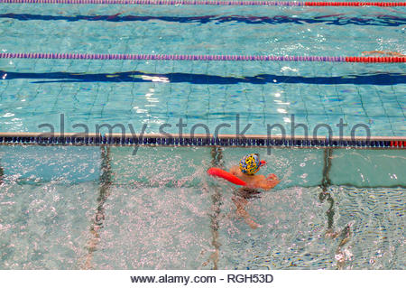 Poznan, Poland - January 26, 2019: Young boy exercising his swimming skills with a swim stick during lesson in the Termy Maltanskie. - Stock Image