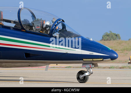 A pilot of the Italian Air Force Frecce Tricolori aerobatic display team waves to the crowd at an airshow - Stock Image