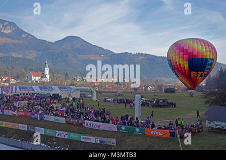 Hot air balloon hovers over field and fans gathered for ski jumping cup in Ljubno ob Savinji. Slovenia. - Stock Image