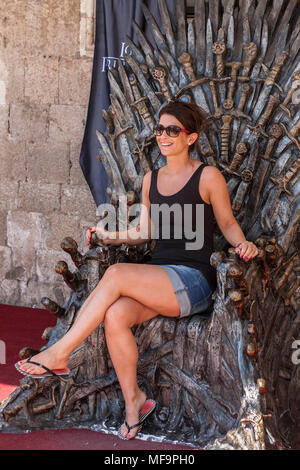 Woman sits on the Iron Throne (from the Game of Thrones), Sponza Palace, Dubrovnik, Croatia.  MODEL RELEASED - Stock Image