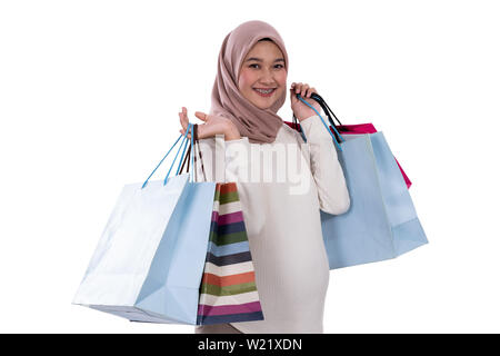 Beautiful veiled woman pregnant carrying lots of shopping bags and smile looking the camera - Stock Image