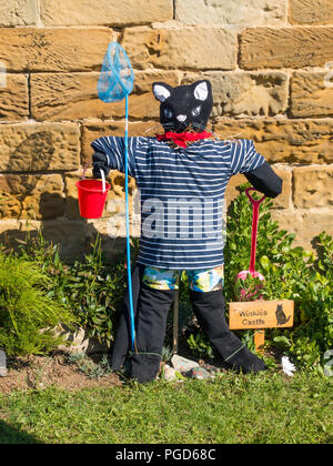 Marske North Yorkshire August 25th/ Like many Yorkshire villages Marske by the Sea has a weeklong Scarecrow Festival which started today 25th August,  many different organisations and social groups have made scarecrows an erected them around the village.  Parents and children can get a trail map to follow and view all the exhibits.  There is a prize draw at the end of the week. This cat is by the local Folk Museum  Winkies Castle in a former cobblers shop it had a cat called Winkie Credit: Peter Jordan_NE/Alamy Live News - Stock Image