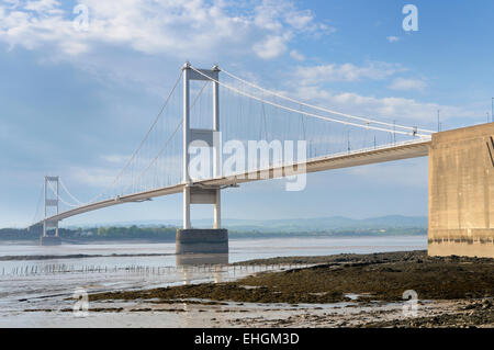 The older Severn suspension bridge spanning the Severn estuary at low tide on a sunny day - Stock Image
