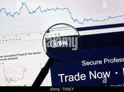 MONTREAL, CANADA - APRIL 26, 2019: BW.com cryptocurrency digital assets exchange logo and home page on a laptop screen under magnifying glass. - Stock Image