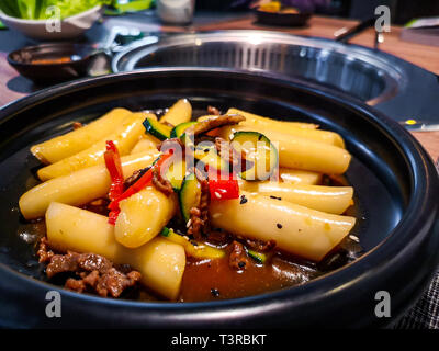 a close up of a Korean Tteokbokki rice dumplings black dish in an korean ethnic restaurant with sweet ganjang soy sauce meat and zucchini bell peppers - Stock Image