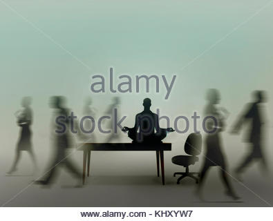 Calm businessman practicing yoga meditation in office while colleagues are rushing around - Stock Image
