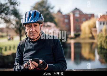 Portrait of senior man with cycling helmet using smartphone - Stock Image