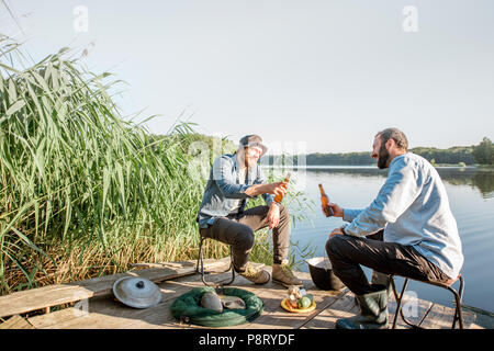 Two male friends relaxing with beer sitting together during the fishing process on the pier near the lake - Stock Image