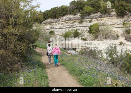 Three children hiking on a nature trail amidst bluebonnets, trees, limestone and a waterfall - Stock Image