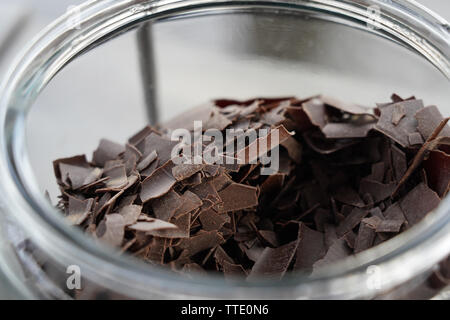 chocolate shavings closeup inside a glass container - Stock Image