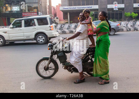 A family on their scooter in the hustle and bustle of downtown Chennai, India - Stock Image