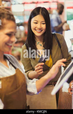 Female cashier helping smiling customer with credit card at grocery store cash register - Stock Image