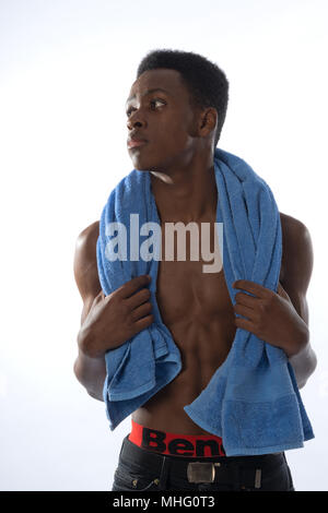 Muscular black man with blue towel over shoulders after exercise - Stock Image