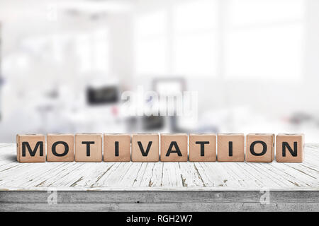 Motivation sign on a desk in a bright office in a business environment - Stock Image