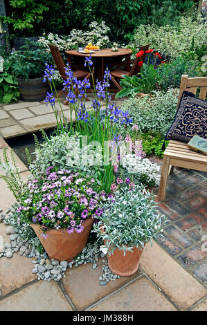 A patio with planted containers and seating for outdoor eating - Stock Image