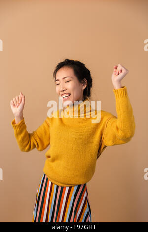 Photo of joyous japanese woman wearing sweater smiling and dancing isolated over beige background in studio - Stock Image