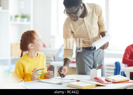 Young teacher consulting little girl while pointing at her notes in copybook at lesson in classroom - Stock Image