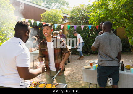 Male friends enjoying backyard summer barbecue - Stock Image
