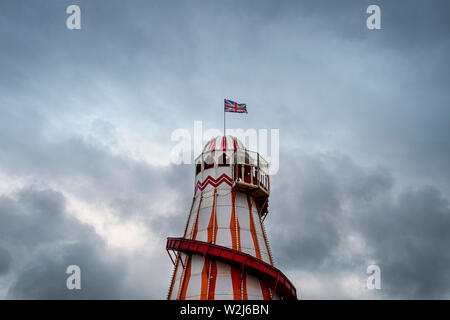Helter-skelter fairground ride with stormy sky - Stock Image