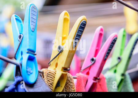 Clothes hanging out on a clothes line to dry with plastic clothes pegs colour matched to the items - Stock Image