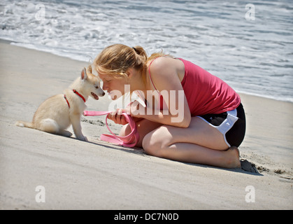 A photograph of a teenager and her new Siberian husky puppy. - Stock Image