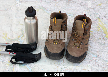 Hiking gear. Walking poles, water flask and trekking boots set on a map in which the words 'National Park' - Stock Image