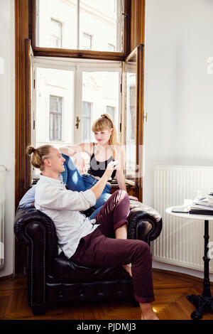 Young couple sitting on living room armchair chatting - Stock Image
