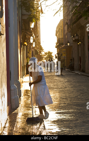 Early morning street scene, Old Havana, Cuba. Washing the strry in front of a building. - Stock Image