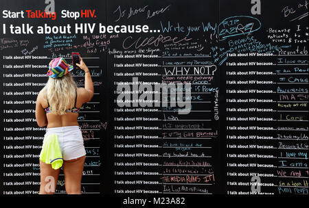 Woman taking photo of a Wall with statements about HIV awareness, 'Start talking. Stop HIV. I talk about HIV - Stock Image