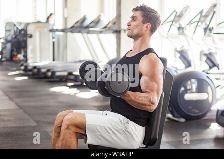 Side view portrait of young adult man muscular built handsome athlete working out in a gym, sitting on a bench and holding two dumbbell with raised ar - Stock Image