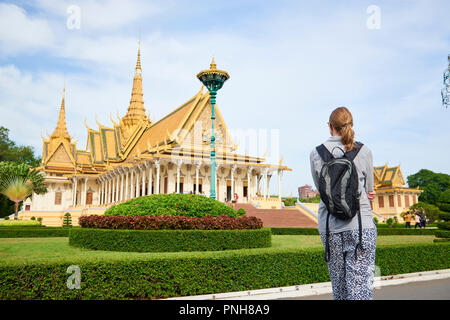 An unidentifiable blonde  caucasian woman looking at the throne hall, one of the buildings inside the Royal Palace complex in Phnom Penh, Cambodia. - Stock Image