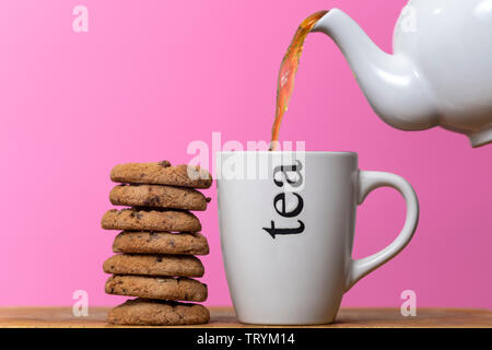 Tea and biscuits, teapot pouring tea into a mug, stack of chocolate chip cookies - Stock Image