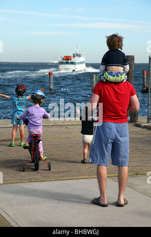 Family bidding farewell to a departing ferry, Fair Harbor, Fire Island, NY, USA - Stock Image