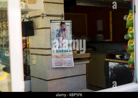 Topless pin-up calendar in a cafe in Lloret de Mar, Spain - Stock Image