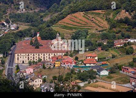 Monasterio de Corias (now a Parador) in the valley of the Río Narcea with terraced vineyards on the slopes. Cangas del Narcea, Asturias, Spain.  [Cang - Stock Image