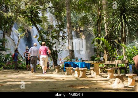 Tourists and picnic tables near upper cascade at Tat Kuang Si waterfalls. Luang Prabang, Louangphabang province, Laos, southeast Asia - Stock Image