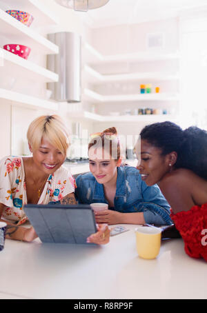 Young women friends using digital tablet at kitchen table - Stock Image