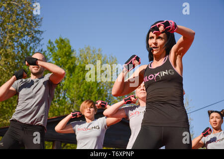 Nis, Serbia - April 20, 2019 Group of young people practicing pose under control of female Piloxing teacher outdoors - Stock Image