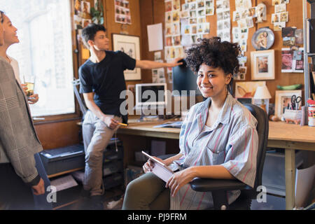 Portrait smiling, confident creative female designer with digital tablet in office - Stock Image