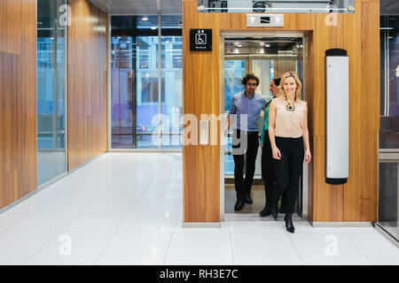 Young coworkers leaving lift - Stock Image