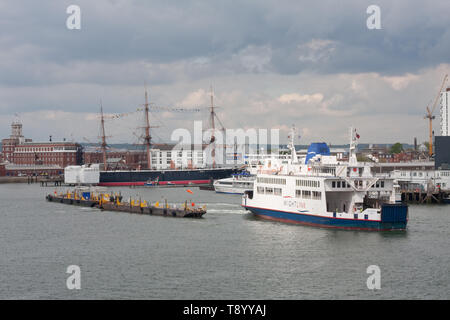 A Wightlink ferry leaves Portsmouth dock wth HMS Warrior 1860 in the background - Stock Image