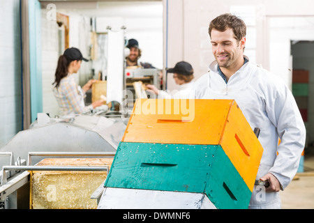 Male Beekeeper Holding Trolley Of Stacked Honeycomb Crates - Stock Image