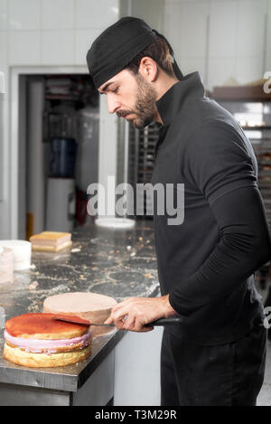 Handsome professional confectioner making a batch of delicious cake in the pastry shop . - Stock Image