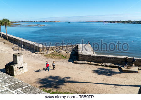 A young couple sits at a point of the seawall at the Castillo de San Marcos, a Spanish fortification at St. Augustine, Florida USA - Stock Image
