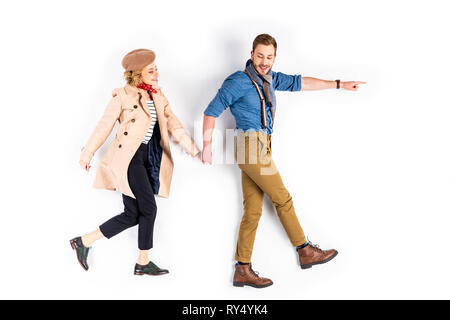 Excited couple holding hands and walking on white background - Stock Image